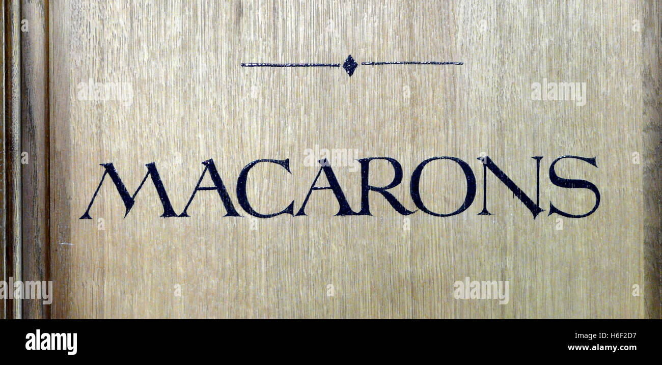 Macarons sign on French patisserie in Paris. Wood panel and blue lettering - Stock Image