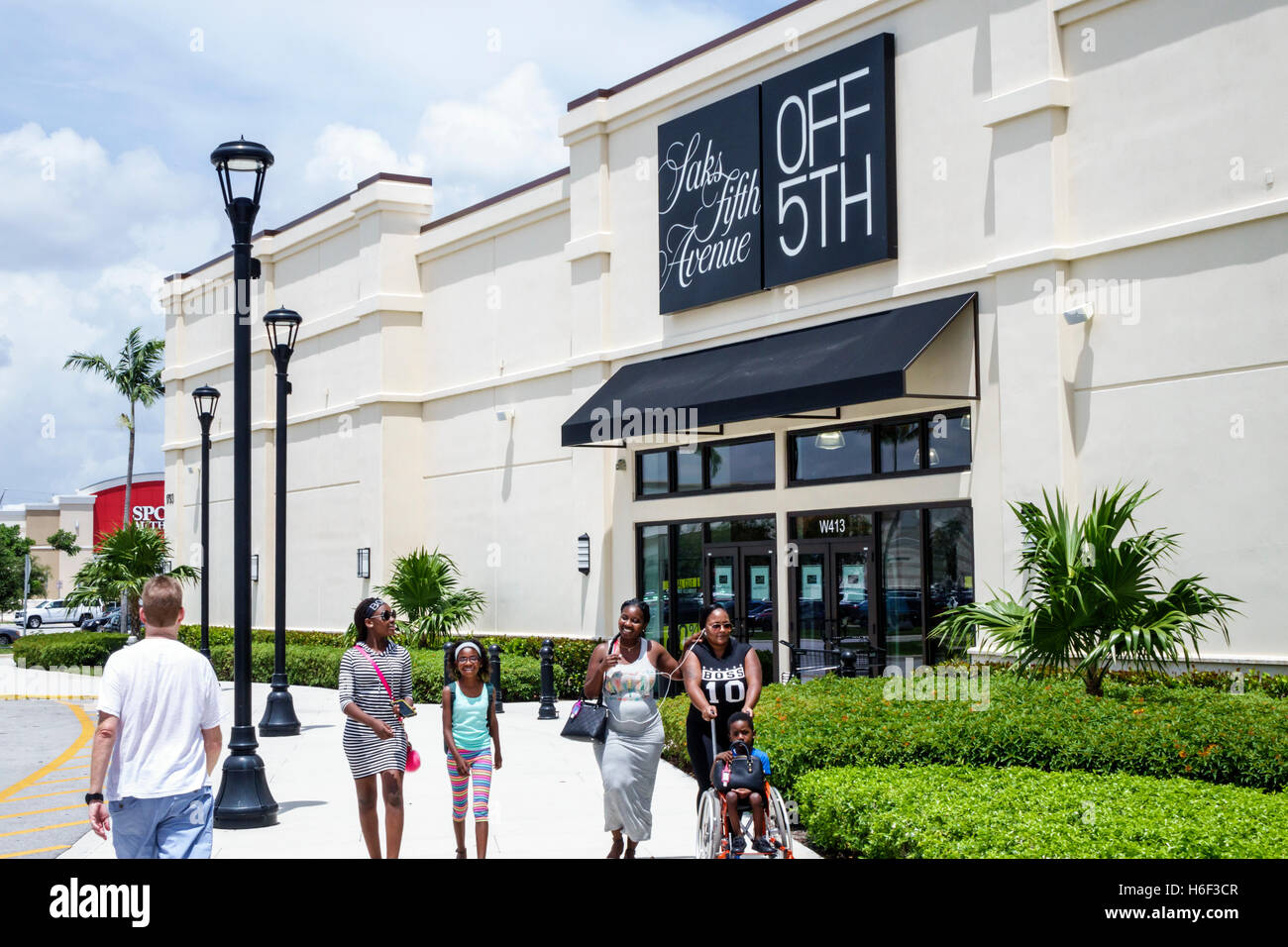 cef16f00cf64 Palm Beach Florida Outlets shopping Saks Fifth Avenue Off 5th front  entrance Black mother girl boy family