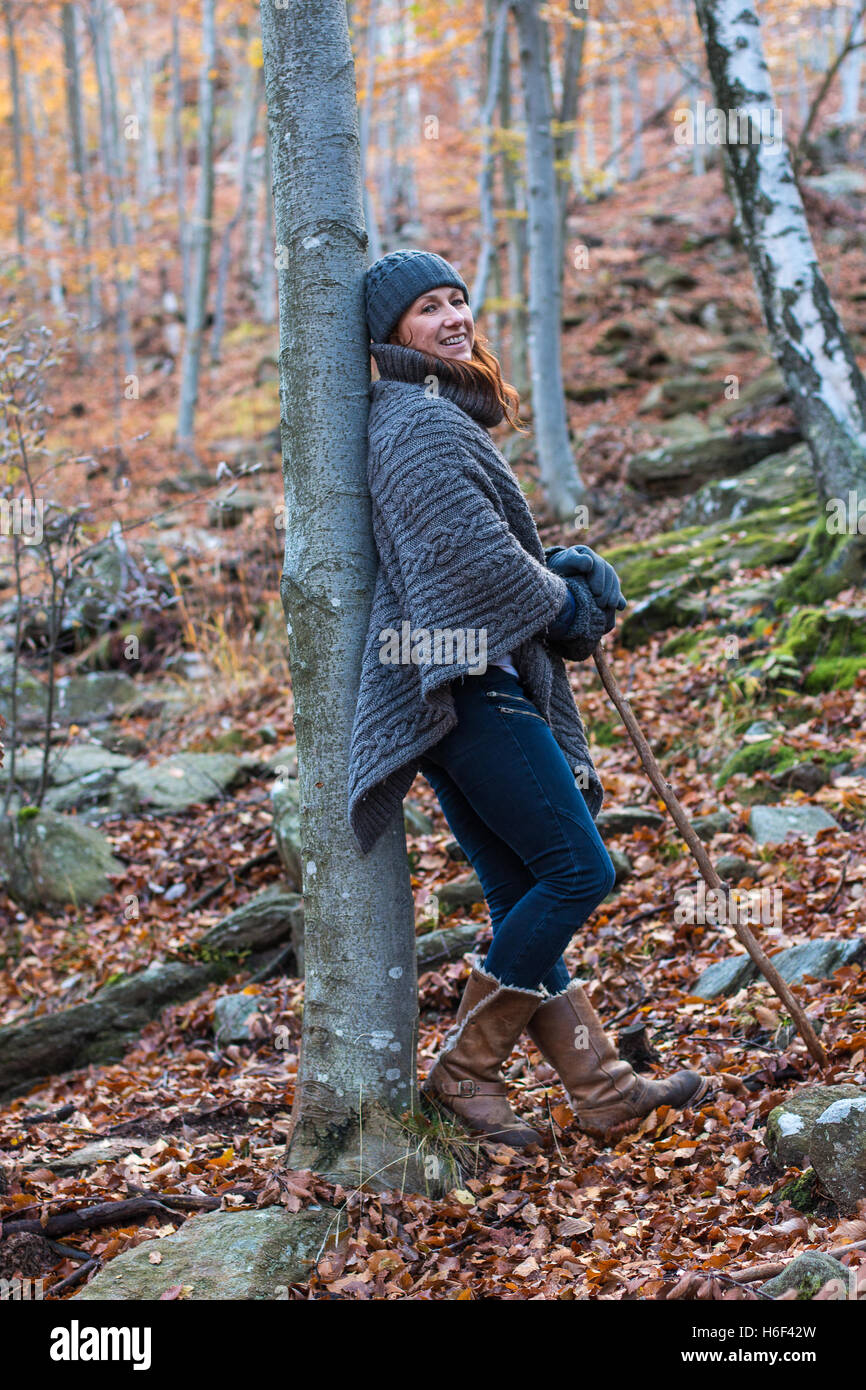 A glamourous woman hiking through the woods in autumn fall season wearing a casual wool poncho leisure wear woolly - Stock Image