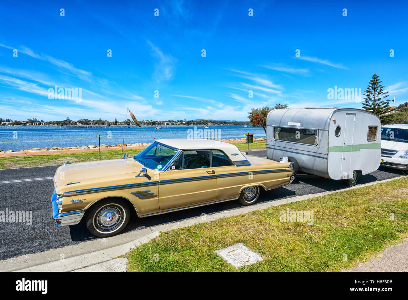 Vintage Mercury Meteor car towing an old style caravan nicknamed 'Gypsy', Merimbula, New South Wales, Australia - Stock Image