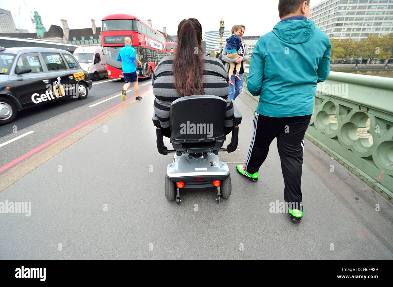 London, England, UK. Overweight woman using a mobility scooter on Westminster Bridge - Stock Image