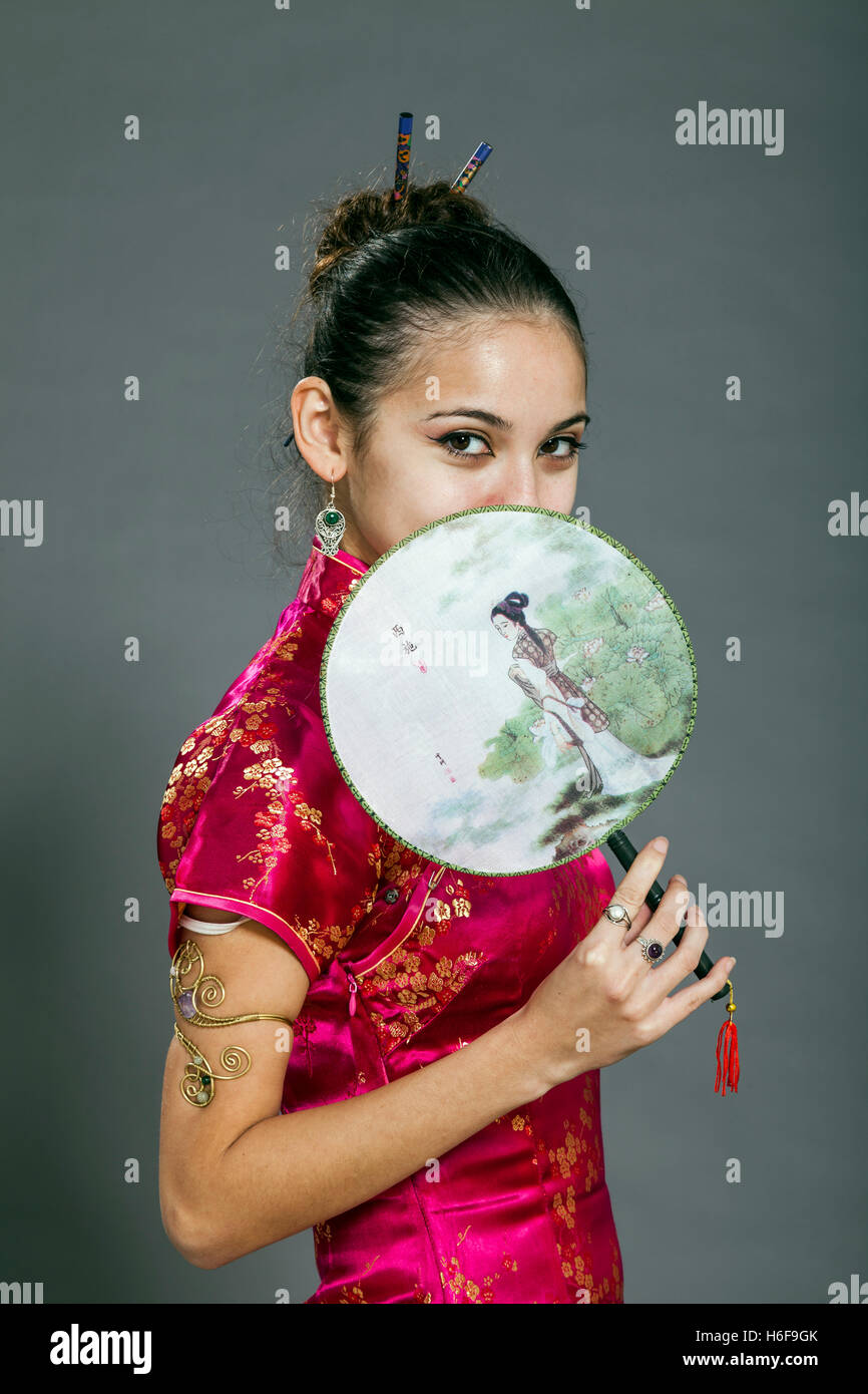 Studio shot of a woman in her early twenties, wearing traditional chinese clothing shy attitude. - Stock Image