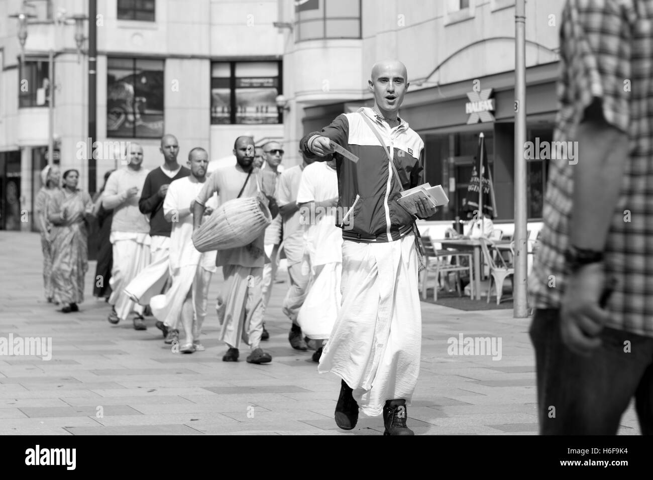 A group of Hare Krishna's chanting while walking through the streets of Cardiff handing out leaflets - Stock Image