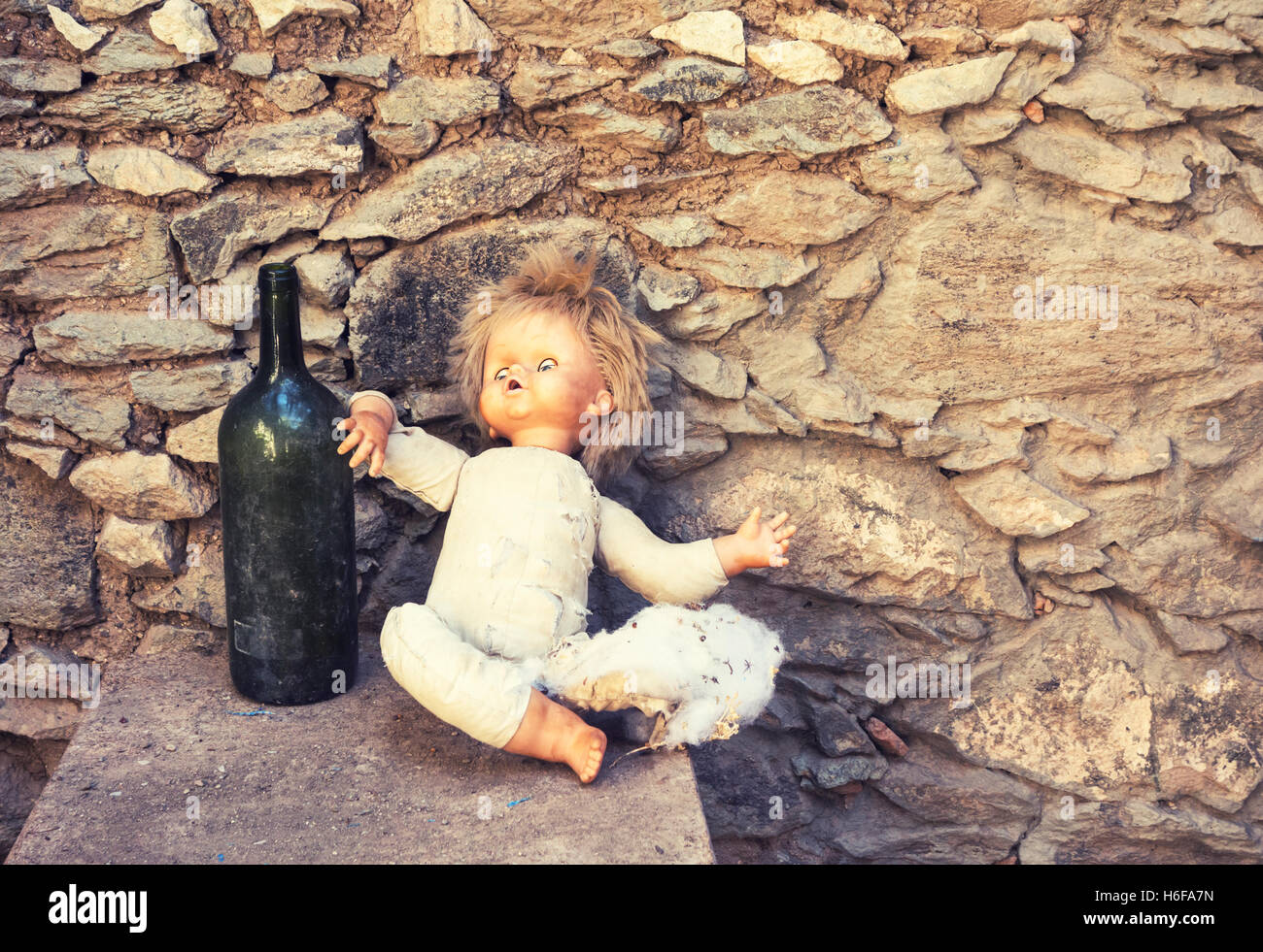 Old doll propped up against empty wine bottle in abandoned mountain house. - Stock Image