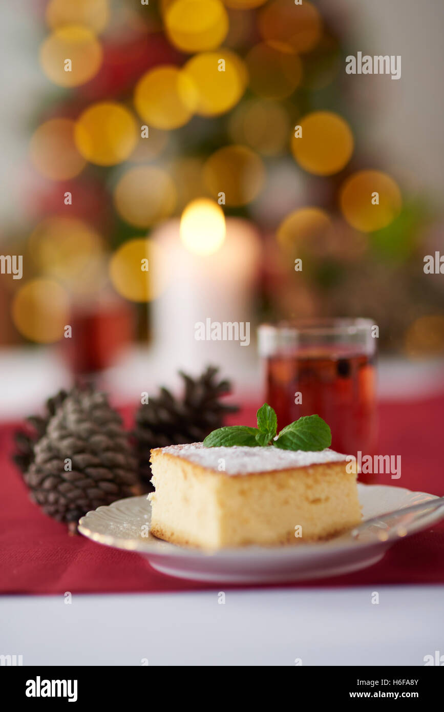 Cheesecake and Christmas tree in the background - Stock Image