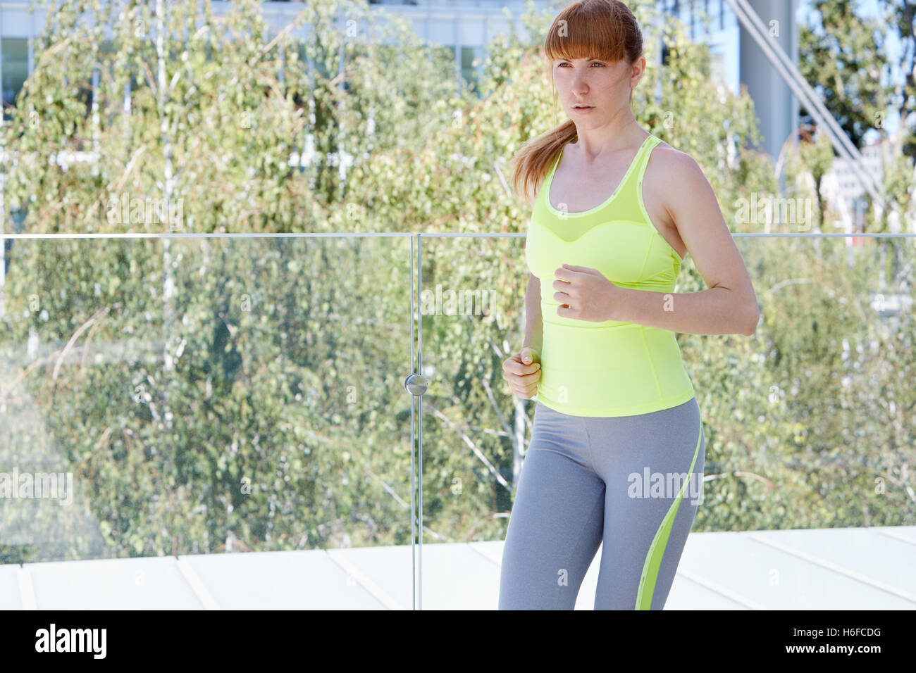 Woman running in modern city in summer with trees background - Stock Image
