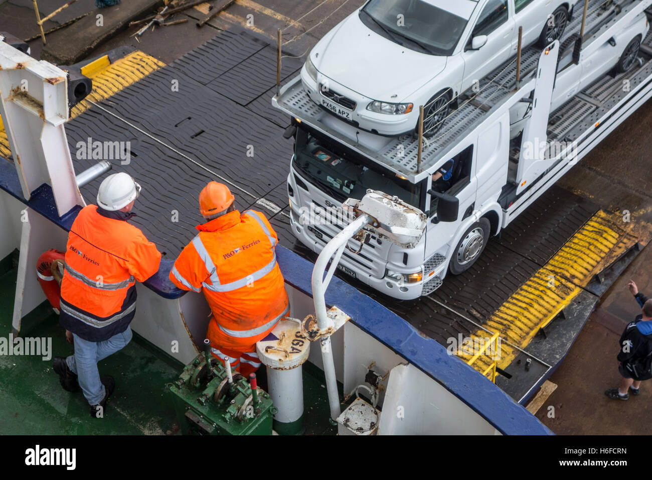 Ship's crew members watching truck with cars on car carrier trailer boarding ferry boat of P&O North Sea - Stock Image
