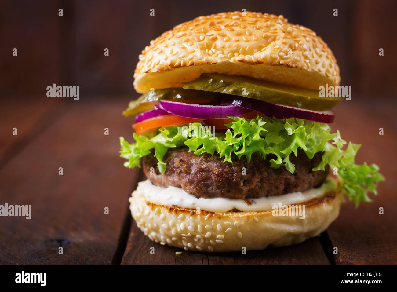Big sandwich - hamburger burger with beef, pickles, tomato and tartar sauce on wooden background. - Stock Image