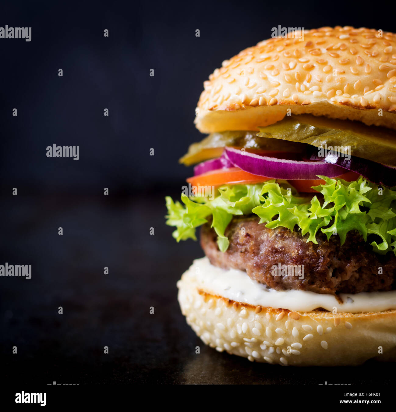 Big sandwich - hamburger burger with beef, pickles, tomato and tartar sauce on black background. - Stock Image