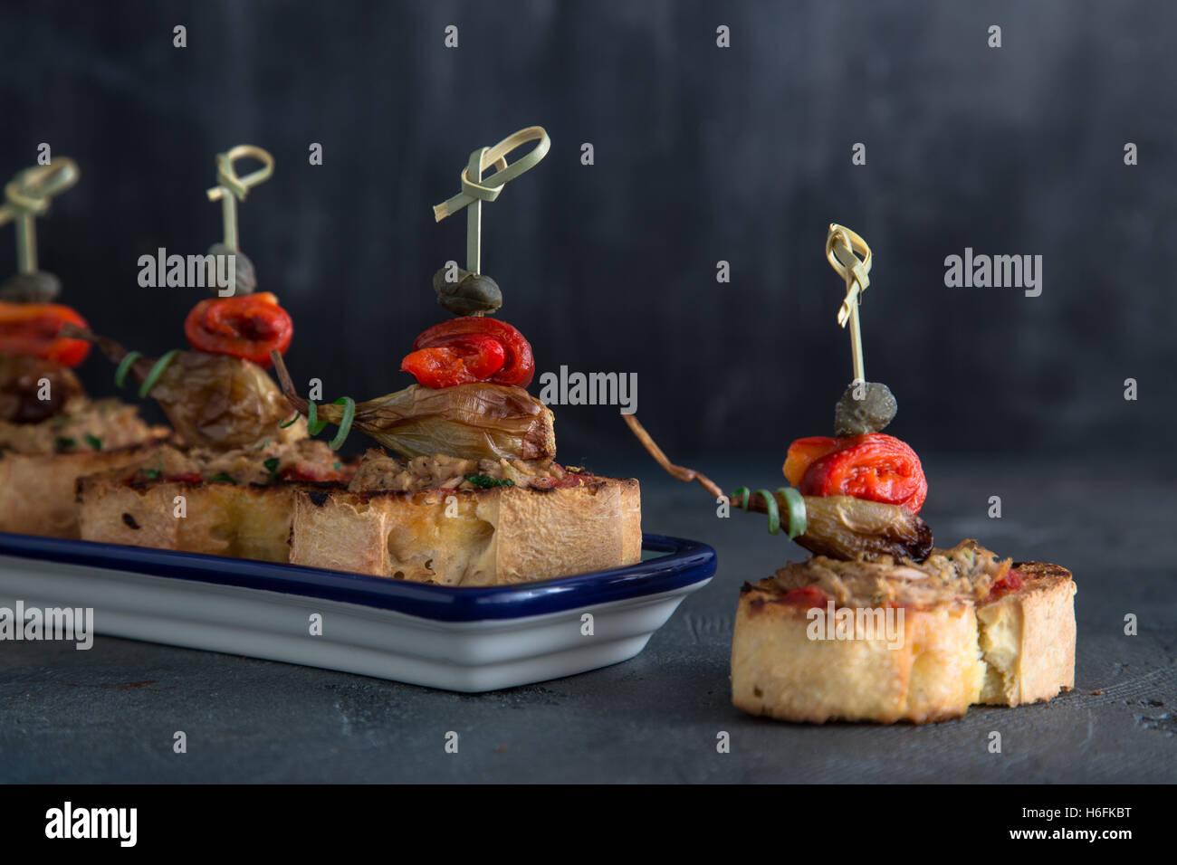 Pintxos Tapa on traditional plate, crispy bread, tuna, onion and pepper. - Stock Image