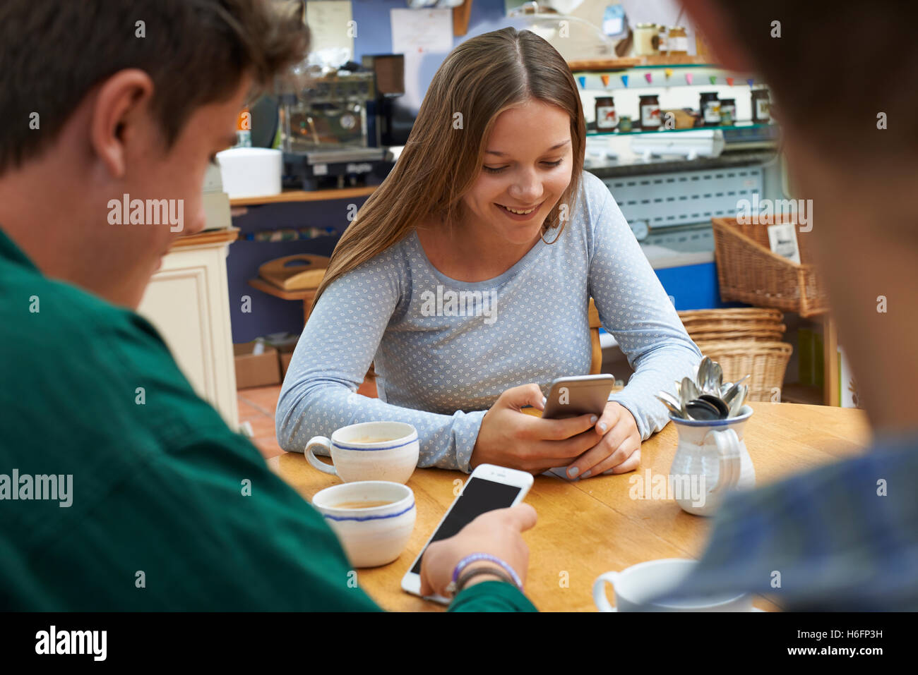 Group Of Teenage Friends Meeting In Cafe And Using Mobile Phones - Stock Image