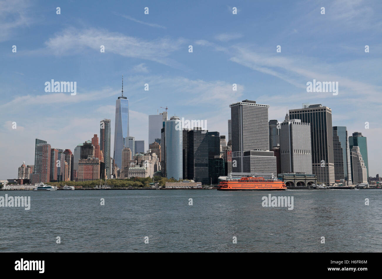 a staten island ferry in front of the lower manhattan skyline. view