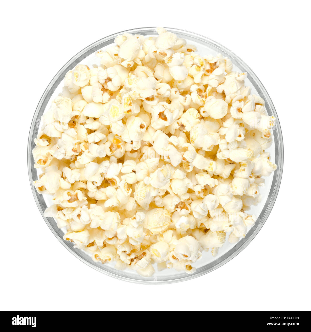 Popped popcorn in glass bowl on white background. Butterfly shaped popcorn puffed up from the kernels, after it - Stock Image