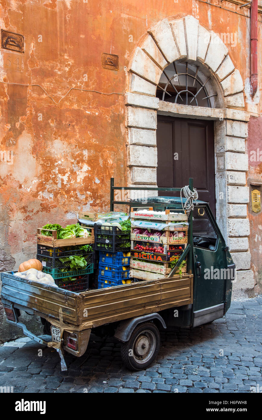 Old Piaggio Ape three-wheeled light commercial vehicle parked in a street of Rome, Lazio, Italy - Stock Image