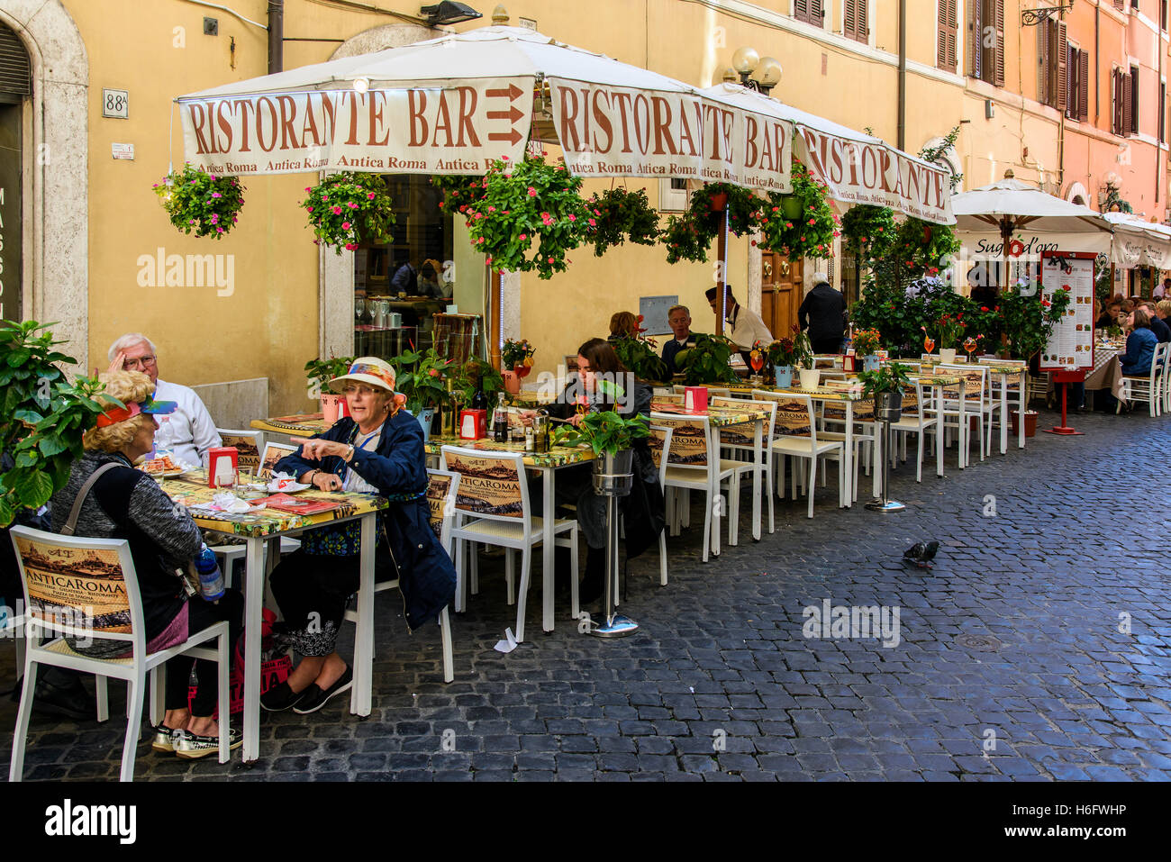 Tourists seated at tables outside a pizzeria restaurant of Rome, Lazio, Italy - Stock Image