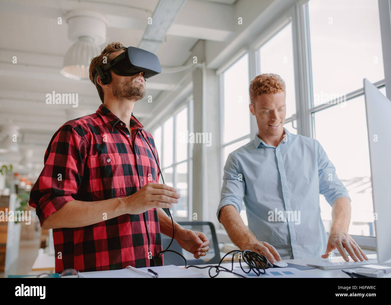 Young developer working on laptop and virtual reality glasses. Two men improving virtual reality glasses in office. - Stock Image