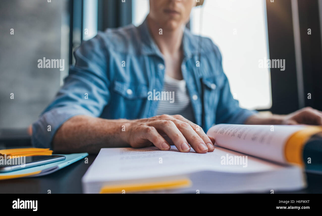 Young man reading book at library, with focus on hand. Male student studying at college library. - Stock Image