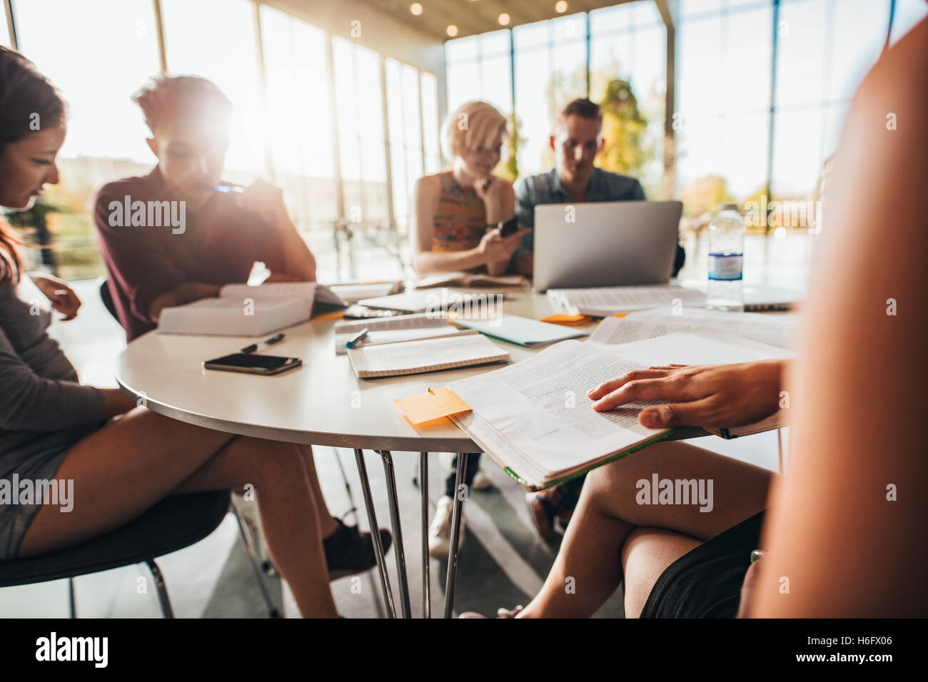 Young students sitting around a table in library with books and laptop. University students studying. - Stock Image