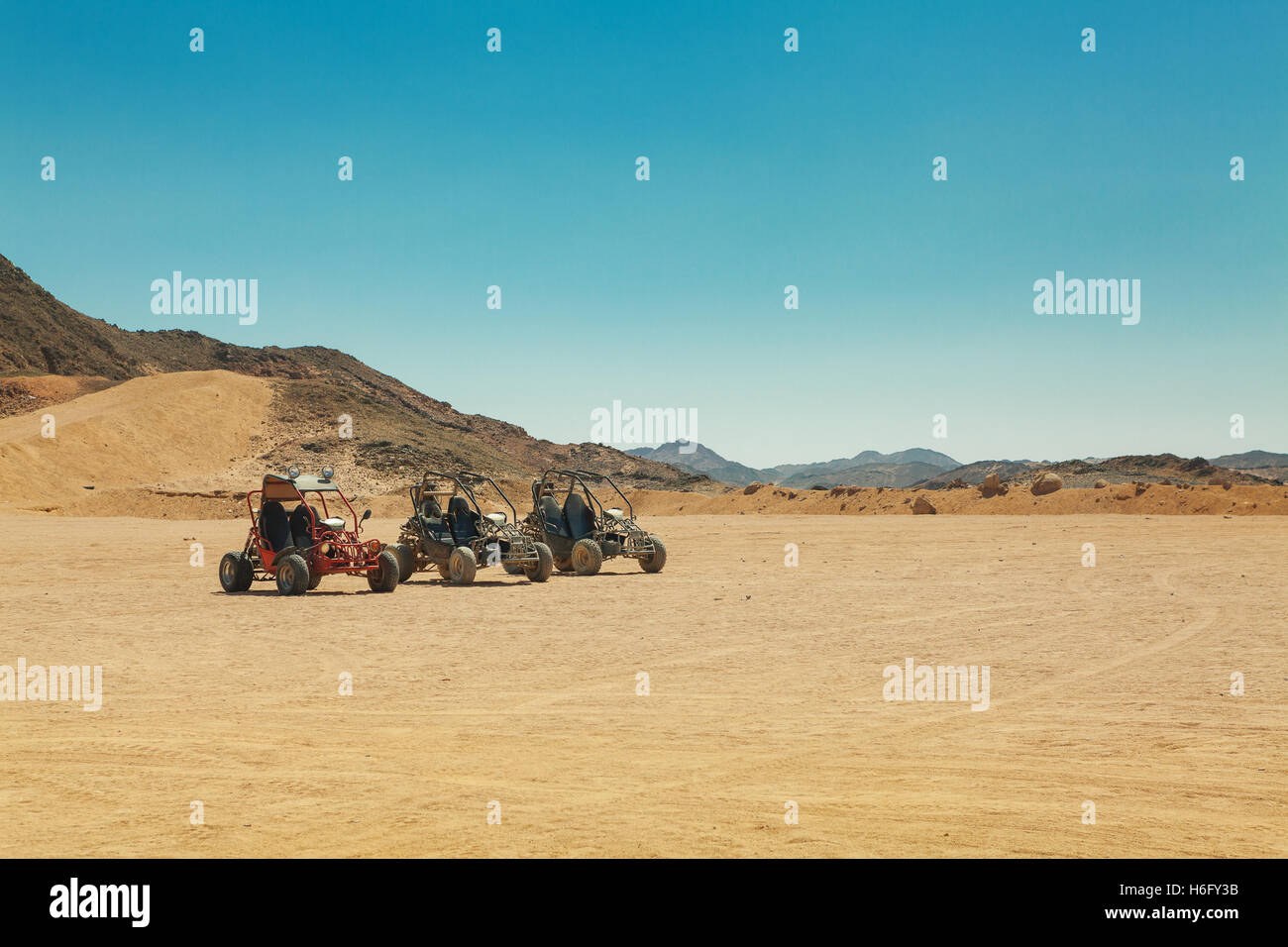 three atv standing in hot desert under clear sky - Stock Image