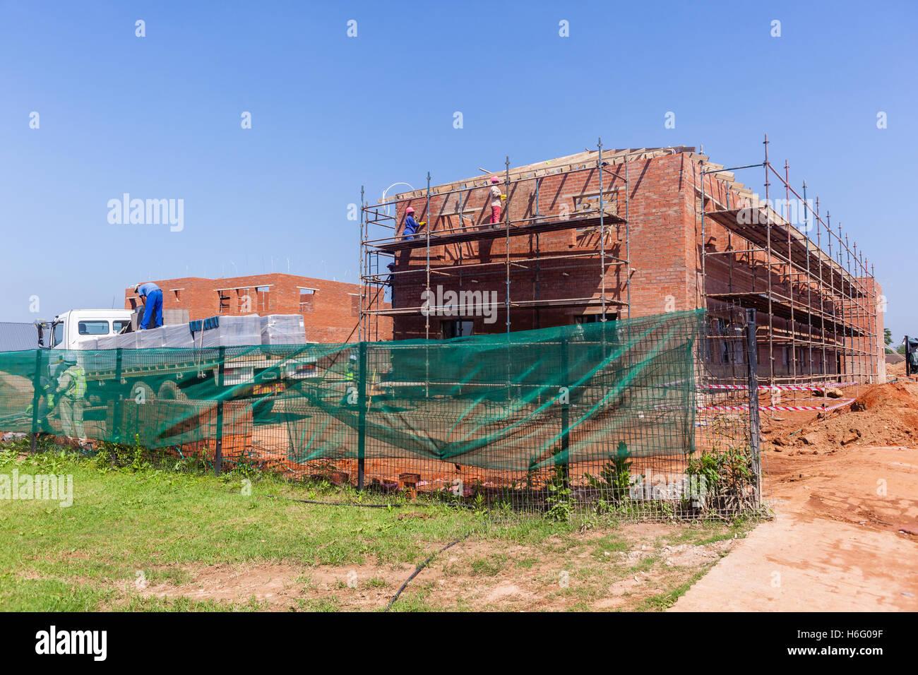 Building construction halfway  photo progress of brick work roof structures. - Stock Image