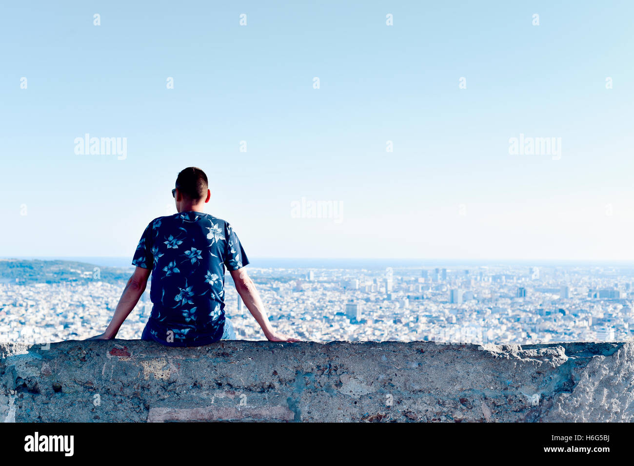 a young caucasian man, seen from behind, sitting at the top of a hill observing the city below him - Stock Image
