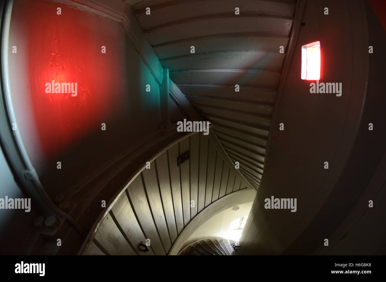 The staircase of a lighthouse, the colour filters taint the light that hits the wall - Stock Image