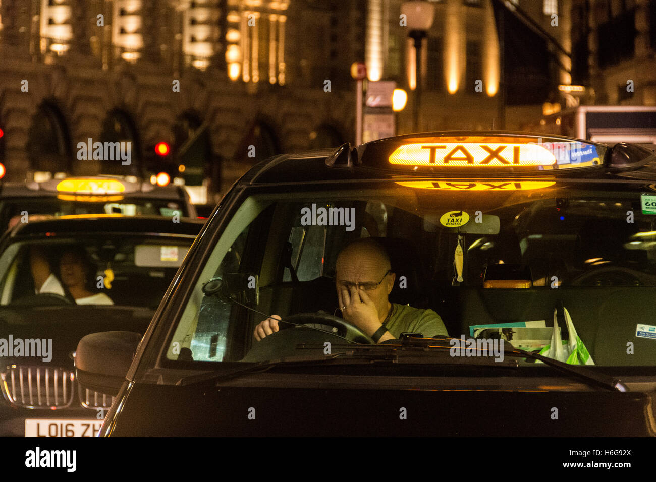 Night time fatigue shows on the face of a London taxi driver in the West End - Stock Image