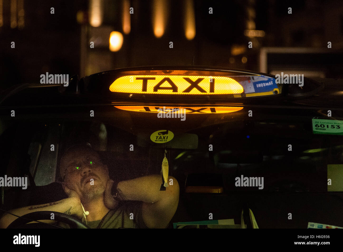 A fatigued black cab taxi driver in London's West End - Stock Image