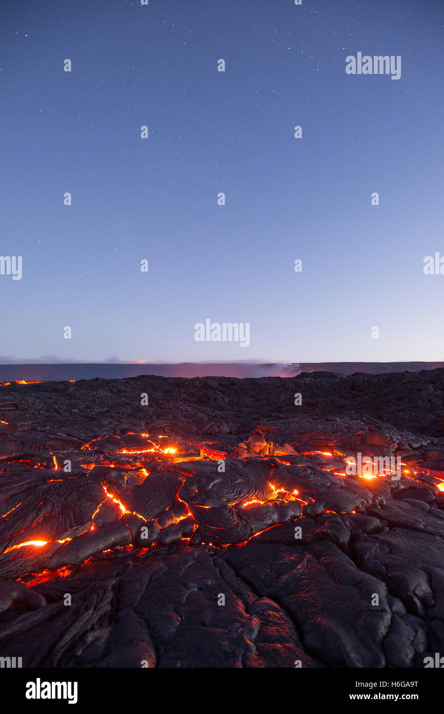 stars fill the pre-dawn sky as hot lava glows through the cracks of pahoehoe in the 61G flow, Hawaii Volcanoes National - Stock Image