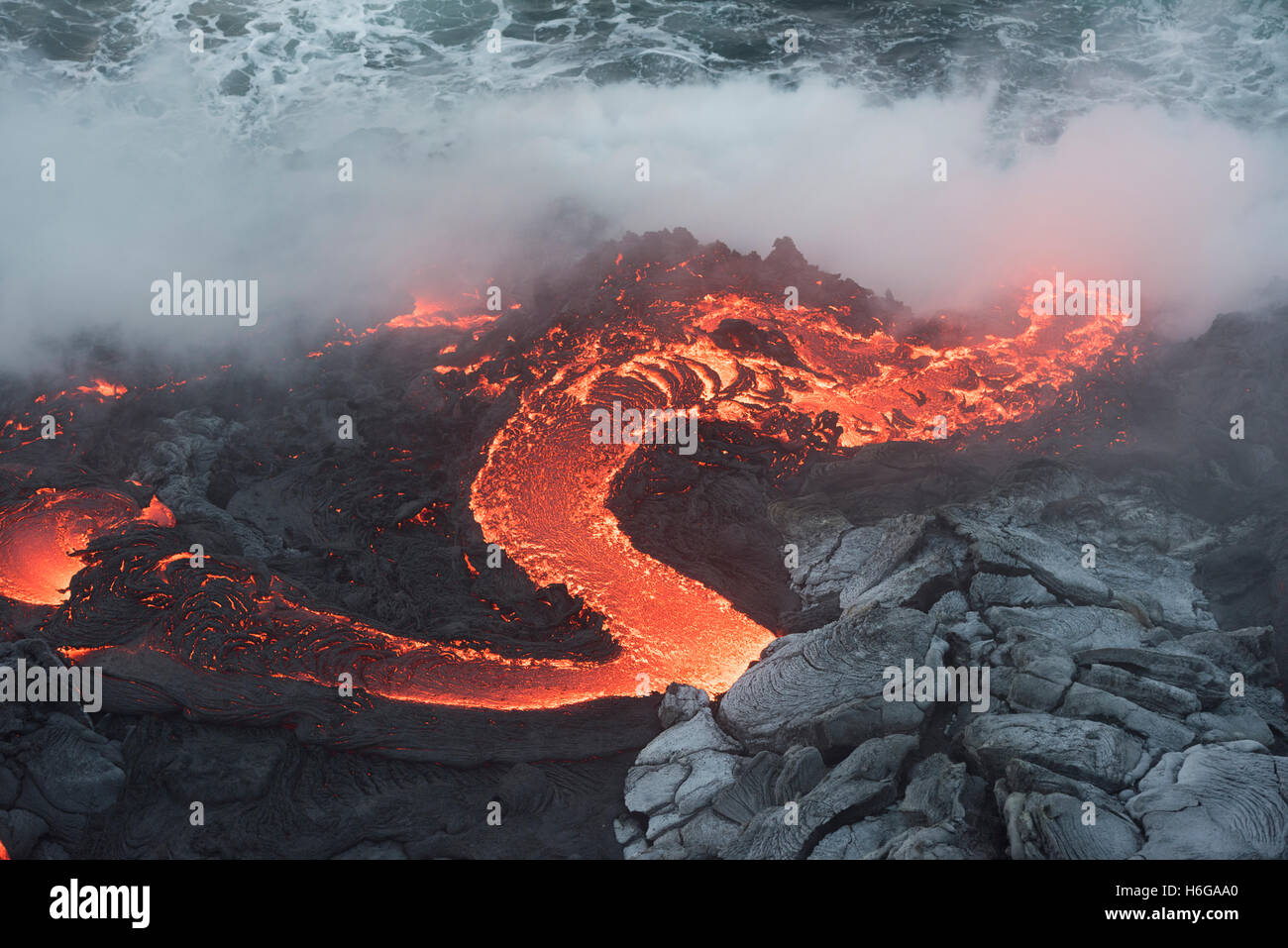 a river of hot pahoehoe lava from the 61G flow, emerges from a lava tube and pours into the ocean at the Kamokuna - Stock Image