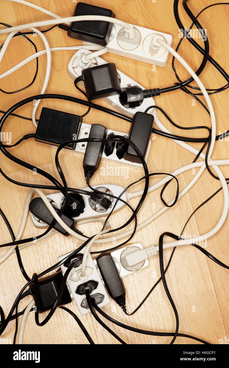 Cables and power adaptors connected to european extension cords. - Stock Image
