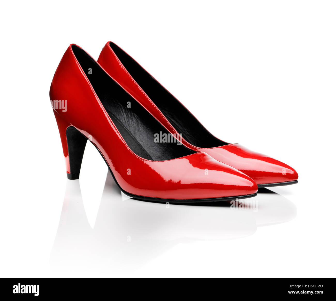 Pair of red women's pumps on white with natural reflection. - Stock Image