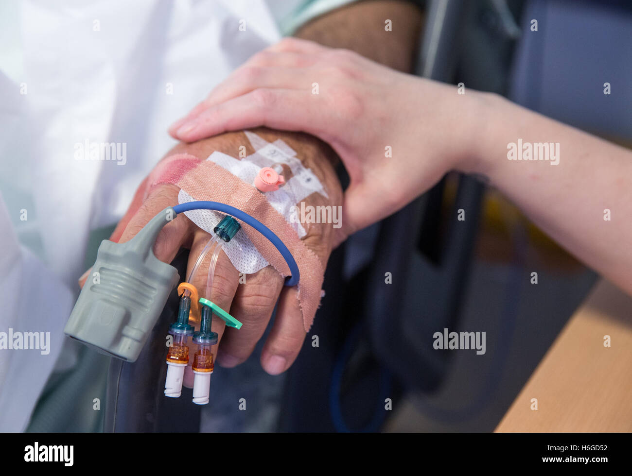 Close-up of Hand of a nurse as she comforts a patients hand with drips and plasters Stock Photo