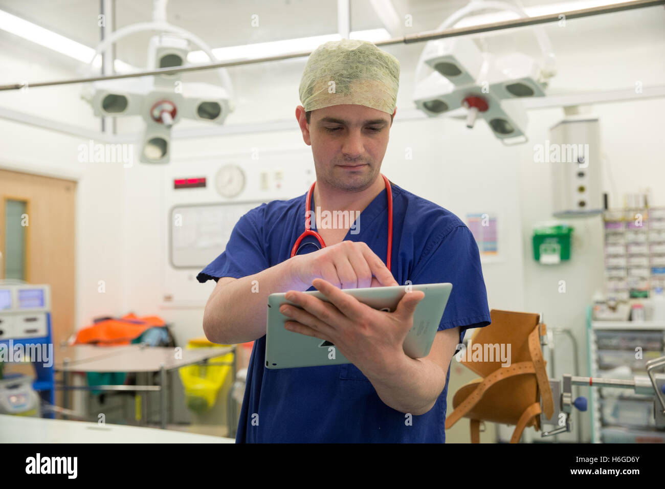 A surgeon in a hospital operating theatre checks the patients' notes on his Ipad prior to an operation - Stock Image