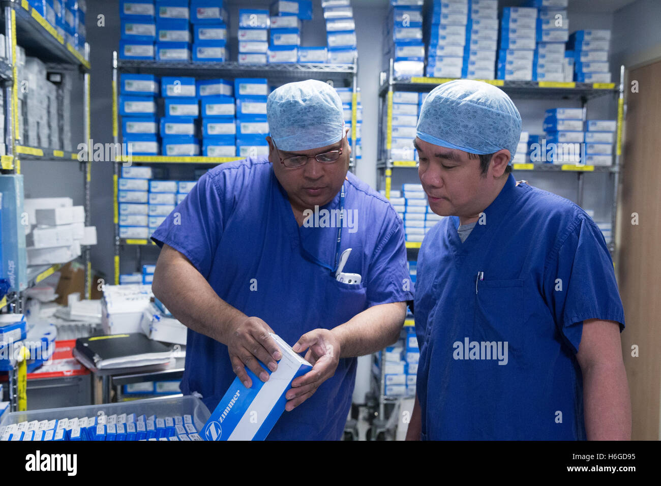 Two nurses in scrubs check medical equipment in the hospital storeroom including hip replacement sterile packs - Stock Image