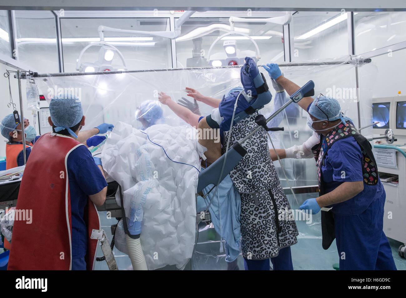 Hospital staff in an operating theatre preparing a patient for a knee operation - Stock Image