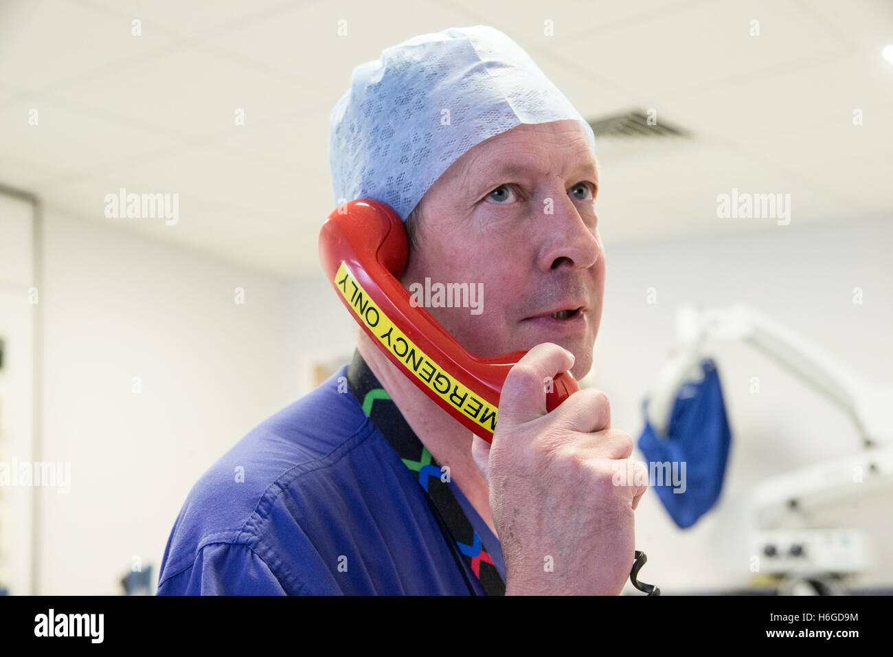 A doctor in a hospital ward uses the emergency telephone to ring for assistance - Stock Image