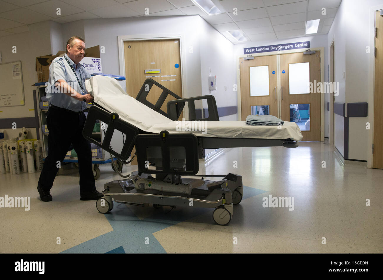A hospital porter wheels an empty trolley through a corridor to collect a patient after an NHS operation - Stock Image