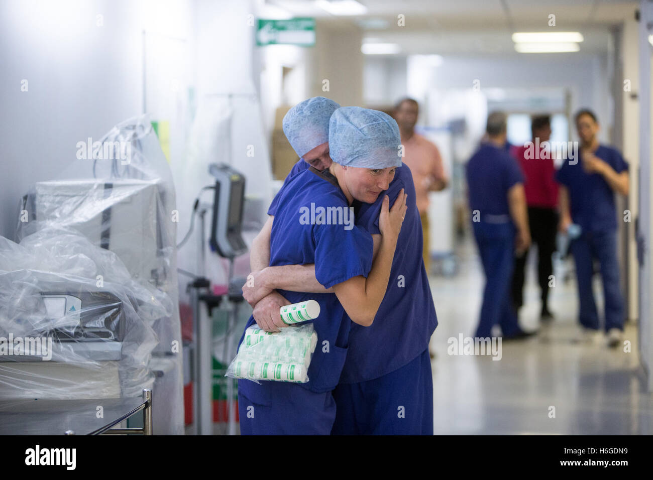 2 doctors hug each other in an NHS hospital corridor after a successful operation - Stock Image