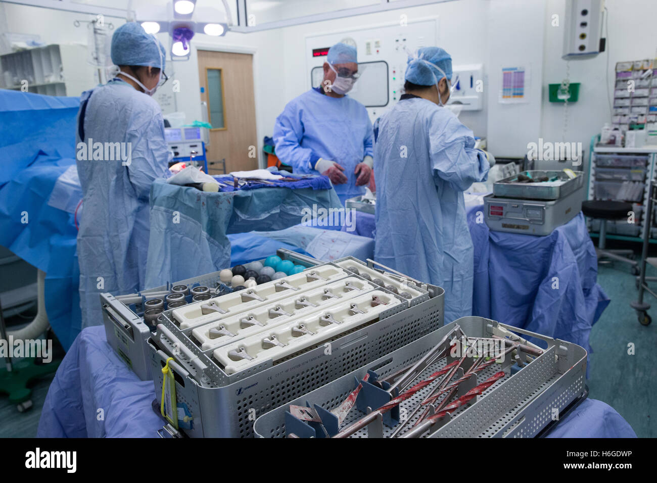 Medical staff in a hospital operating theatre during an knee replacement operation.Drills and equipment are in the Stock Photo