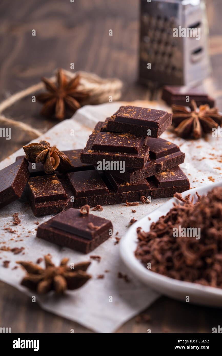 Heap of chocolate pieces with anise and small grater on the background - Stock Image