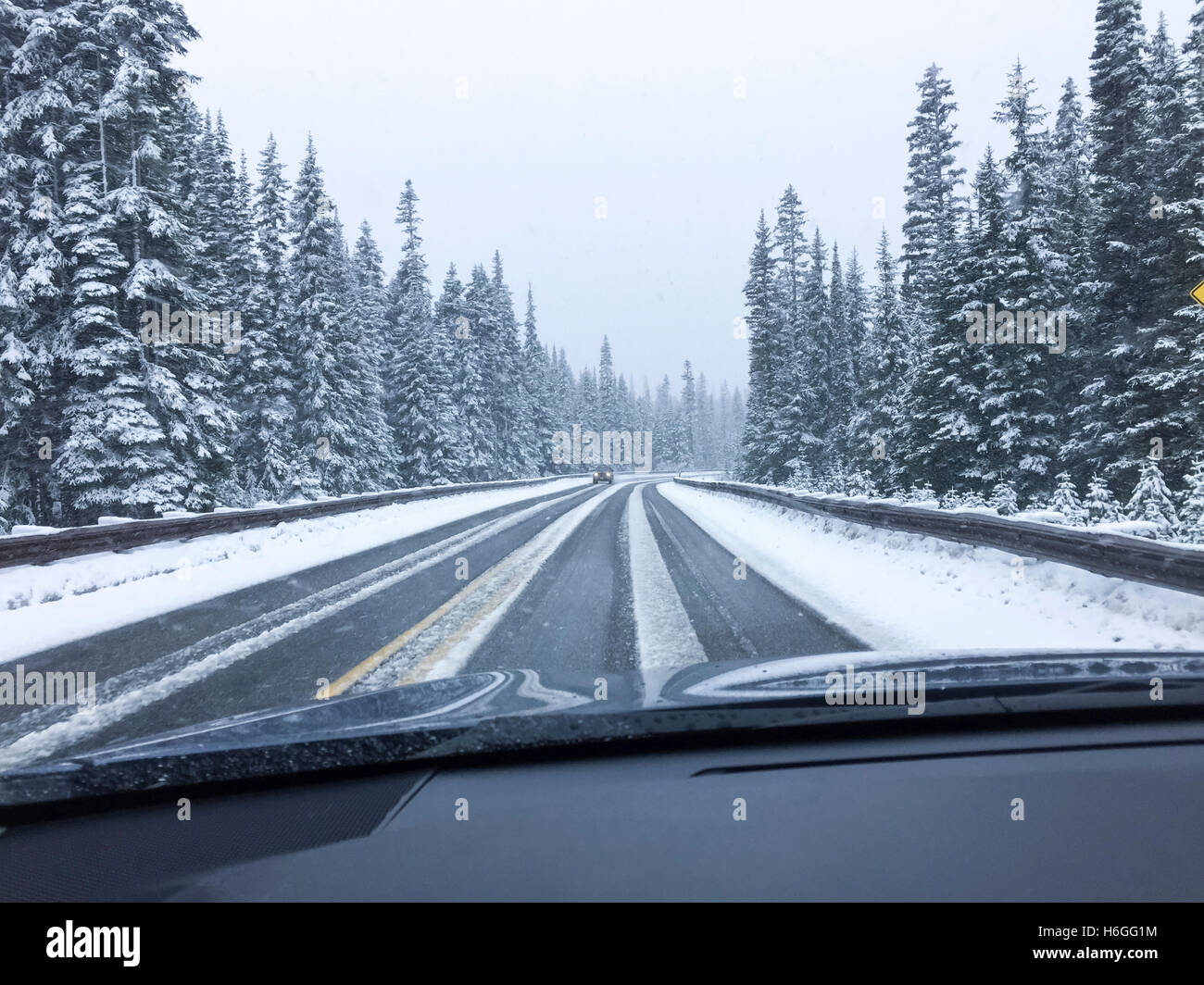Driver's point of view viewpoint looking through car windshield of snowy road in winter driving - Stock Image