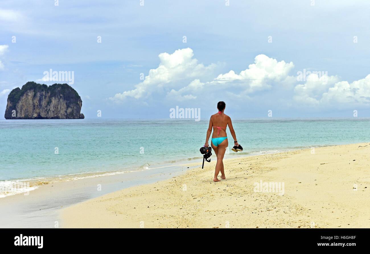 Bikini clad woman walks along an island beach in Thailand, carrying a snorkel set - Stock Image