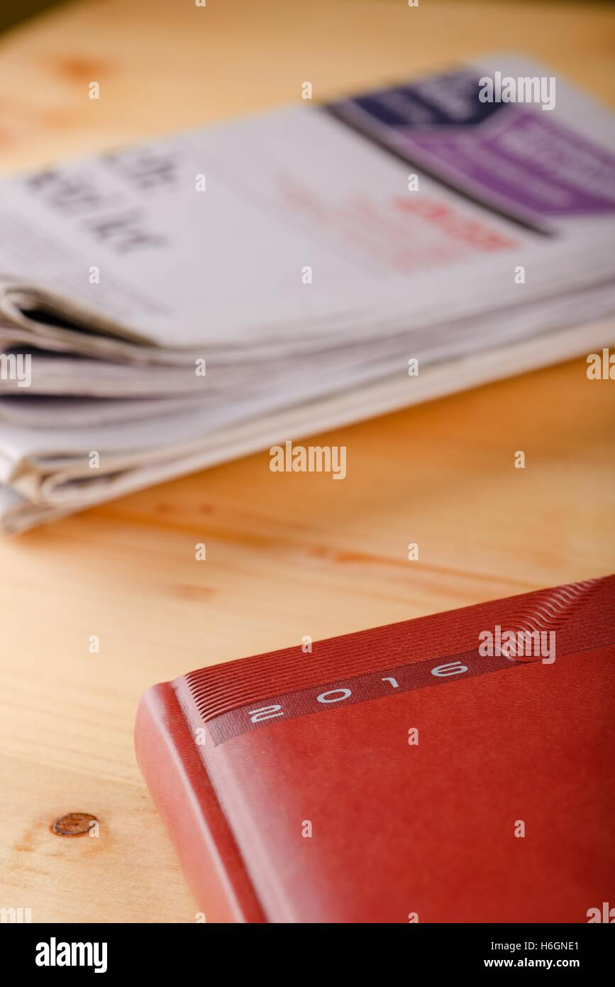 Vertical photo of red diary for year 2016 which is placed in a corner of light wooden boad in front of several newspapers - Stock Image