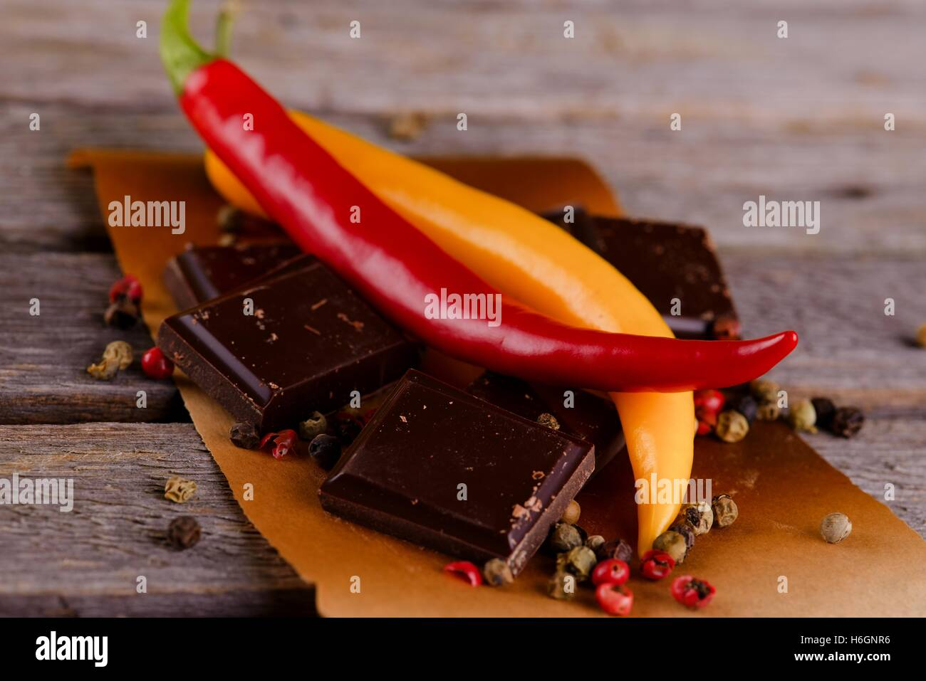 Horizontal photo of two chili peppers red and yellow placed on pieces of dark chocolate with several seeds around. - Stock Image