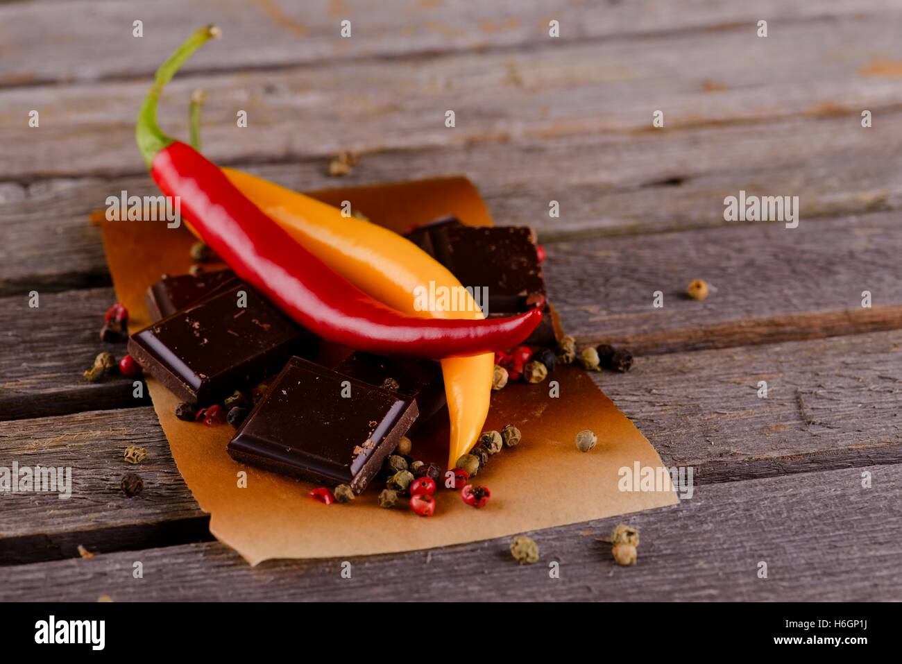 Horizontal photo of two chili peppers with yellow and red color and dark chocolate pieces on piece of paper with - Stock Image