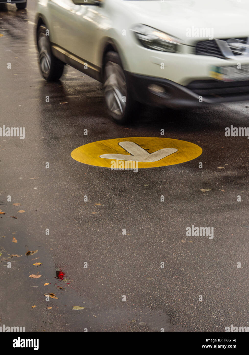 Car rides on the a wet road, which draw an arrow indicating the ...