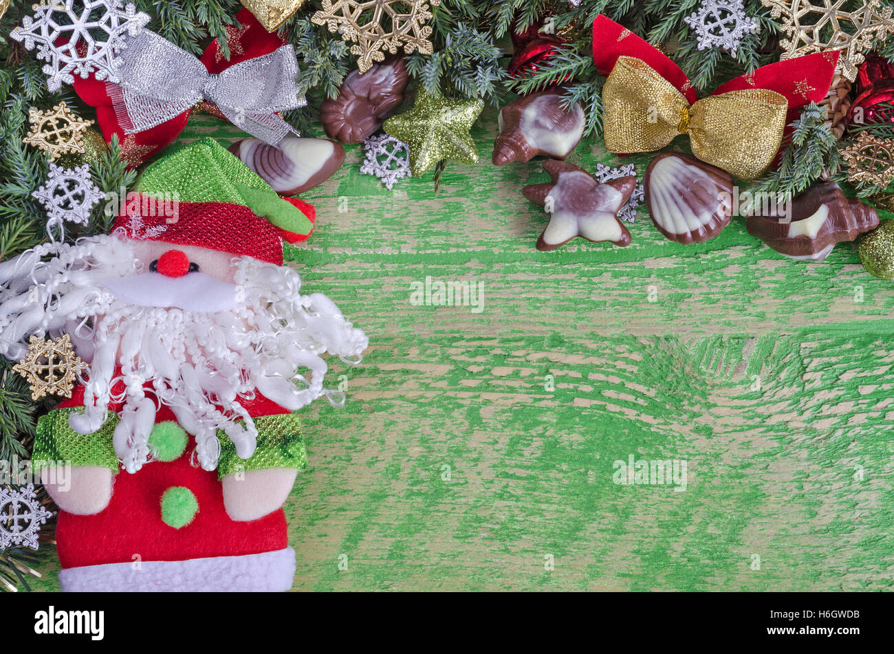 Christmas decorations, Santa Claus and chocolate. Old green wooden ...