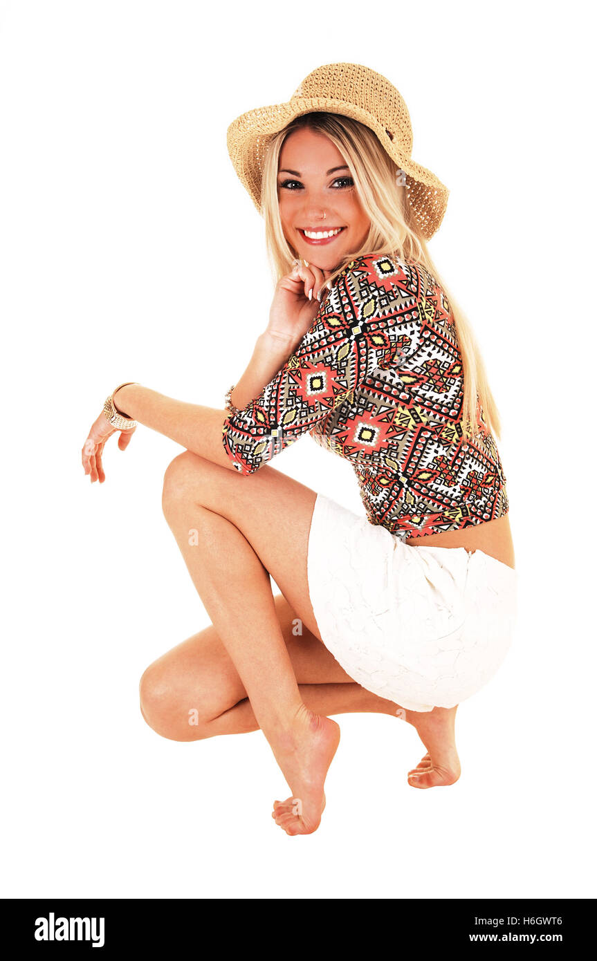 A beautiful happy blond woman in a white skirt and beige hat crouching on the floor for white background. - Stock Image