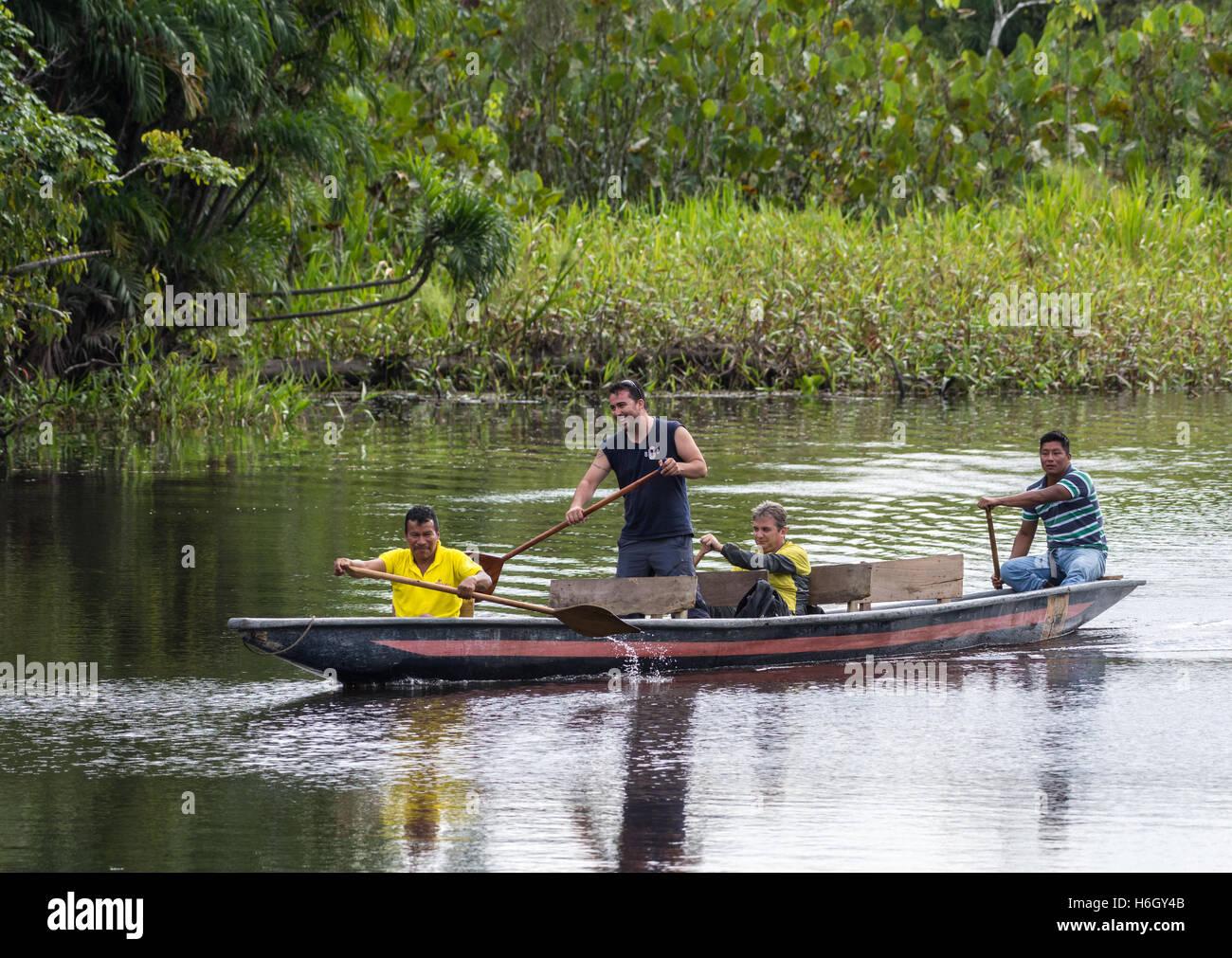 Native Kichwa tribal men guide tourists in Amazon rain forest in a paddle canoe. Yasuni National Park, Ecuador, - Stock Image